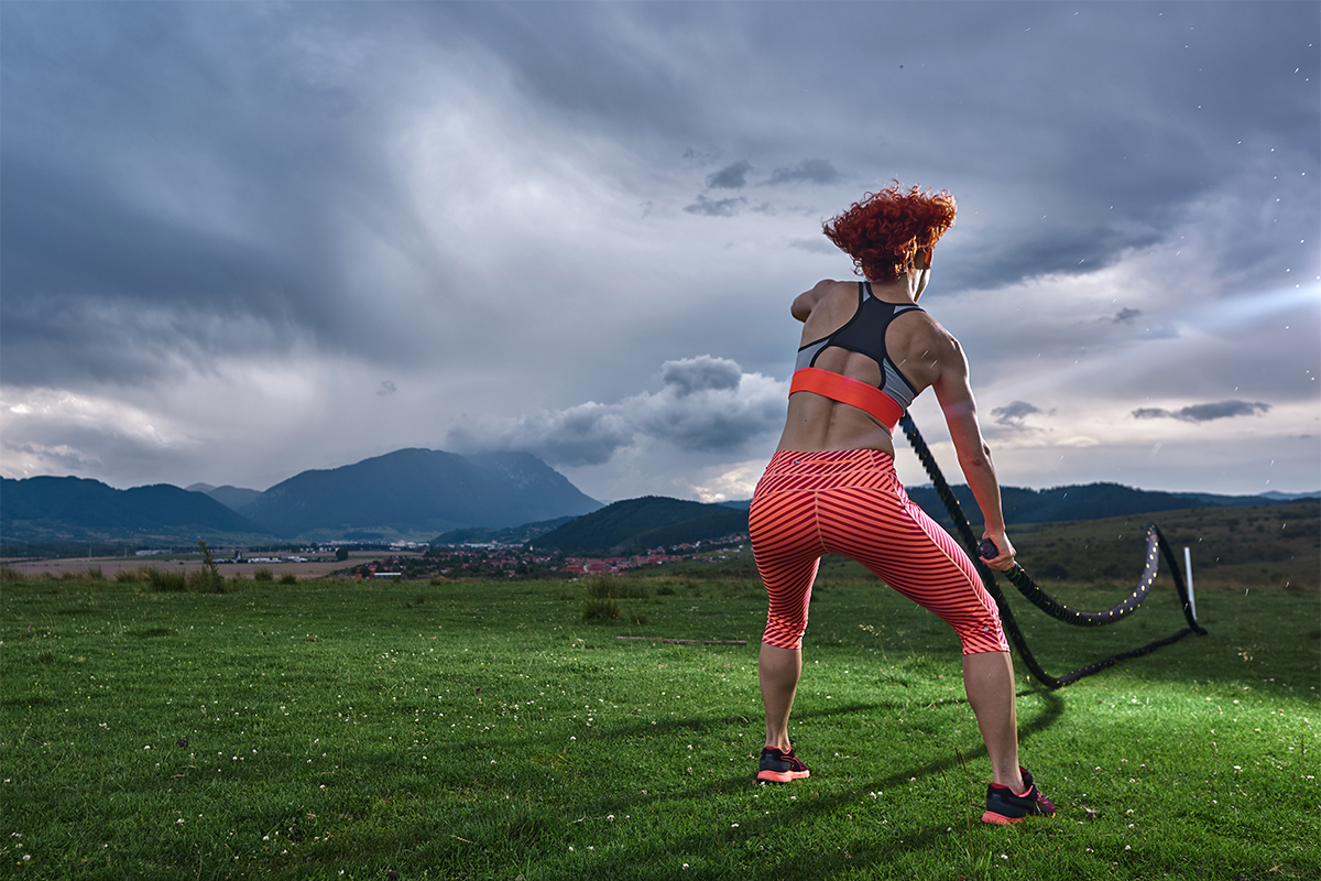 Woman doing battle rope HIIT workouts outside