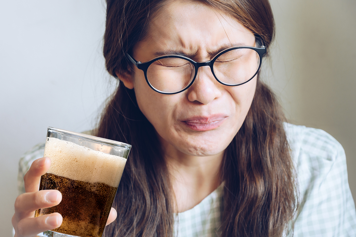 Woman drinking sweet drink with fructose and wincing