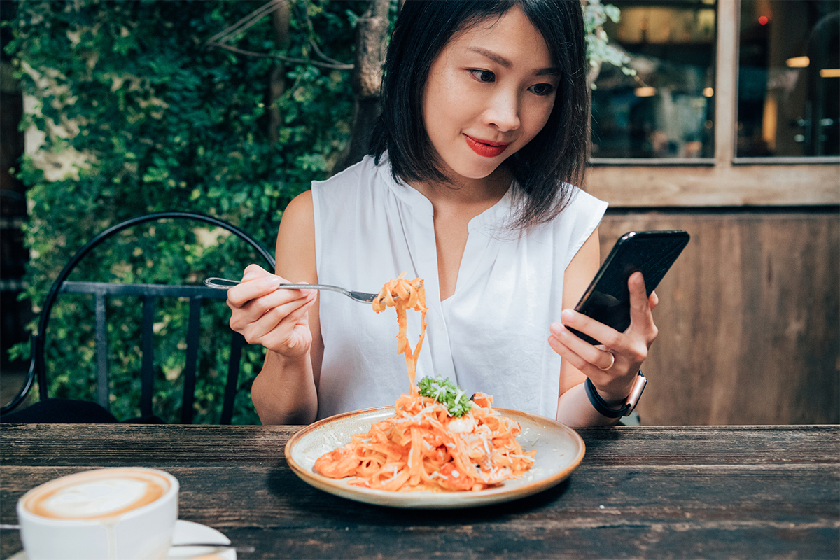 A woman overeating while distracted with a phone