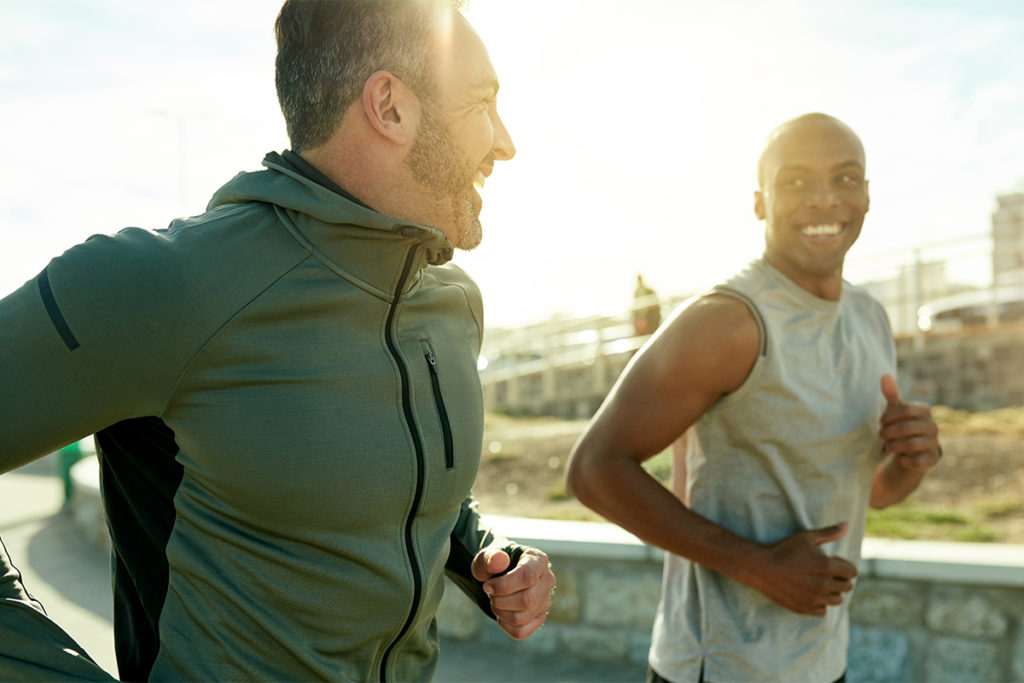 Two men running together smiling to show link between exercise and mental health
