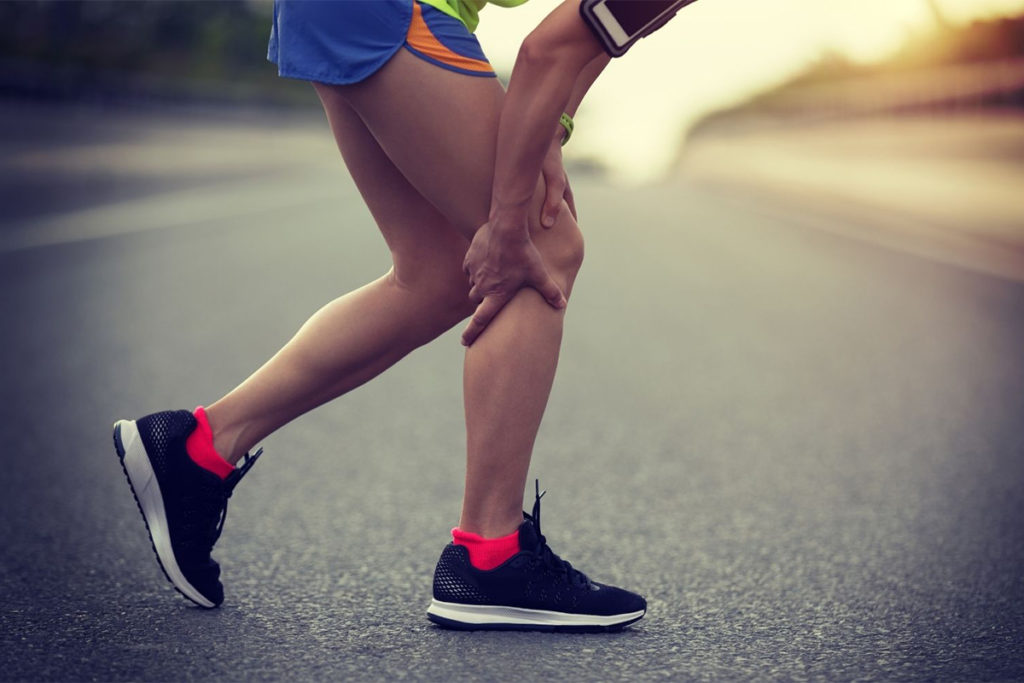 Person gripping their leg in pain on a run
