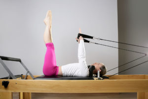 Woman performing Pilates training on a reformer.
